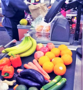 Fruit and vegetables with no bags, on a conveyor belt at a supermarket checkout.